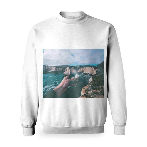 Person Holding Smartphone Capturing Pictures Of Body Water Beside Rock Formations Under Cloudy Sky During Daytime Basic Sweatshirt