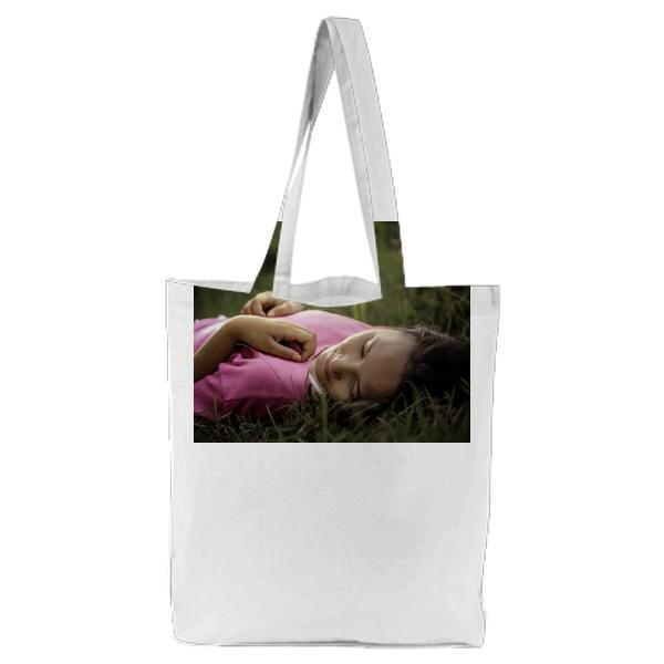 Woman Lying On Green Grass Tote Bag