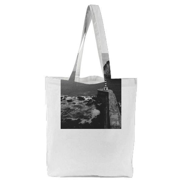 White And Black Tower Near The Sea Under White Sky Tote Bag