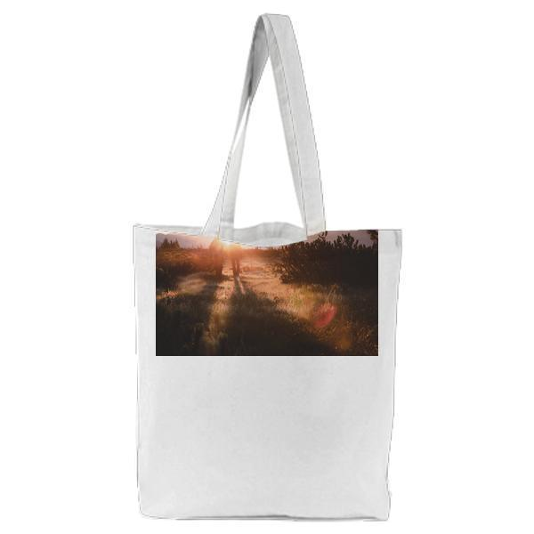 2 People Walking On Grass Field In Front Of Mountain During Sunrise Tote Bag