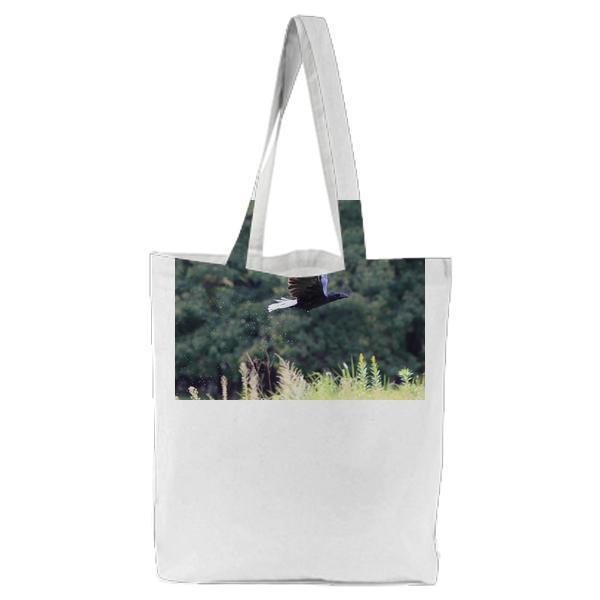 Black Bird Flying Near Green Grass During Daytime Tote Bag