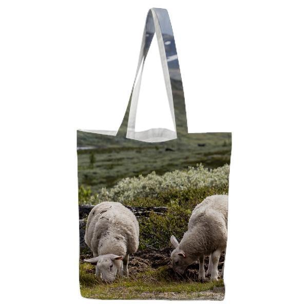 3 White Sheep Standing Near On Green Grass In Front Of Mountains Tote Bag