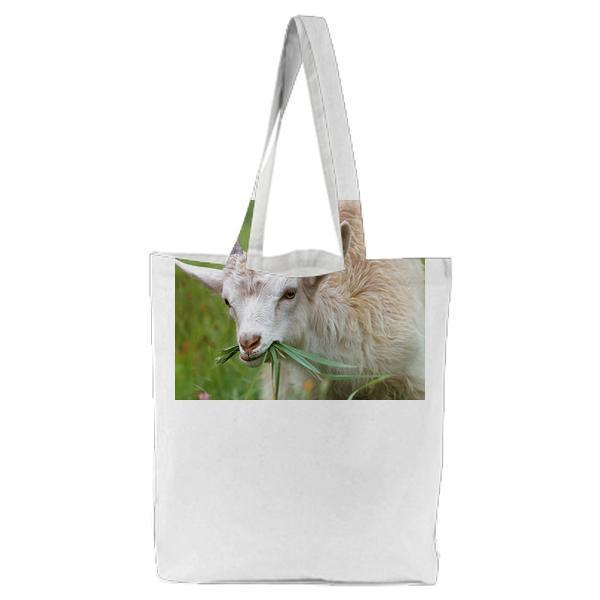 White Goat Eating Grass During Daytime Tote Bag