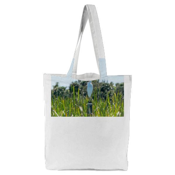 White And Yellow Bird On Pole Beside Grasses During Daytime Tote Bag