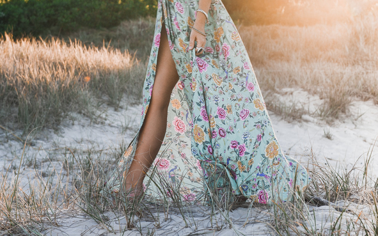 The legs of a woman walking on the beach in a blue floral maxi dress from Arnhem Clothing