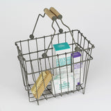 Wire basket with handles in grey featuring bathroom products