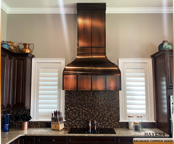 Copper range hood with a farmhouse kitchen sink, granite counters, and copper lighting