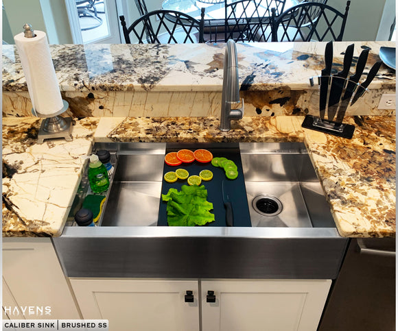 Custom farmhouse stainless steel sinks with a built-in ledge for advanced sink accessories.