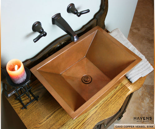 Cavo vessel copper sink on top of an antique wood vanity with oil-rubbed bronze faucets.