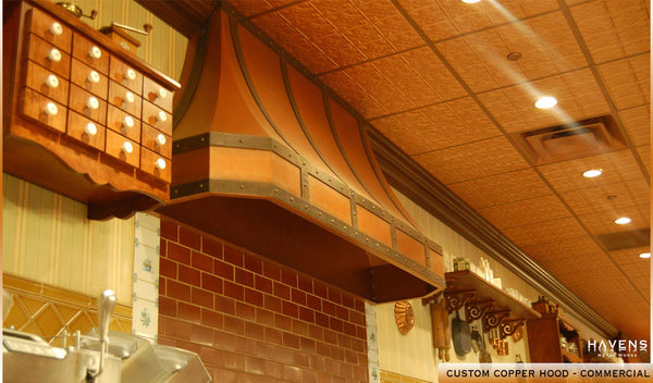 Copper range hood installed in a commercial kitchen with a need for powerful ventilation.