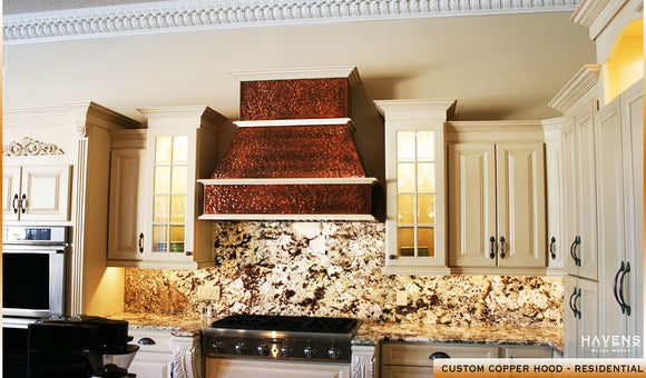 Hammered copper kitchen hood with stone backsplash in residential kitchen, built and installed by Havens.