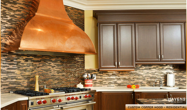 Beautiful and prominent copper kitchen hood installed with dark cabinetry.