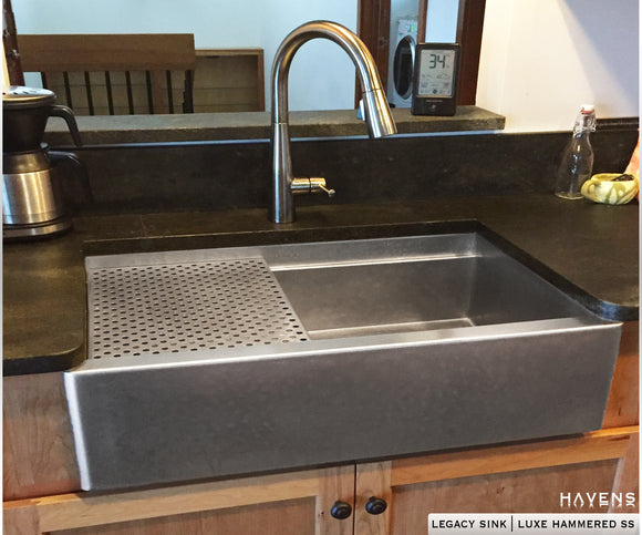 Custom stainless farmhouse sink with a hammered stainless steel finish.