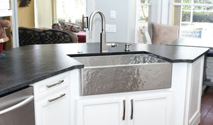 Hammered stainless steel farmhouse sink in a luxury kitchen, built by Havens.