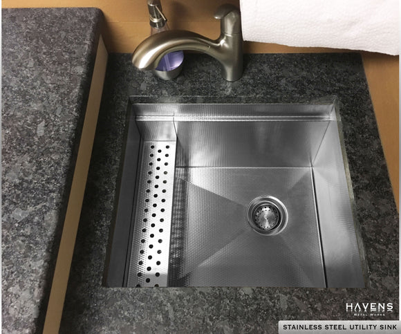 Custom stainless steel utility sink with a built-in ledge for an advanced user experience.