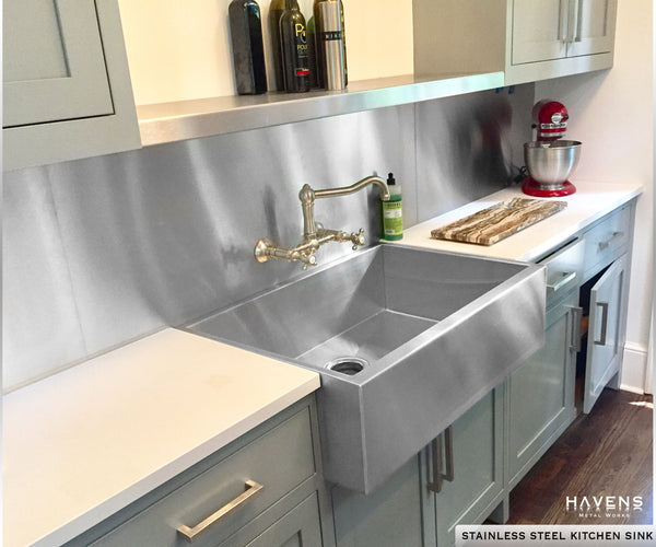 Kitchen with stainless steel topmount sink. Custom depth and farmhouse apron front.