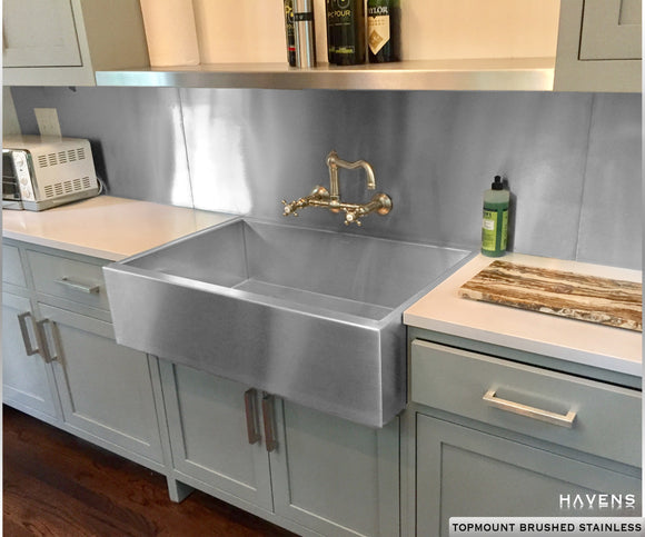 Custom retrofit stainless steel sink with a prominent farmhouse apron front.