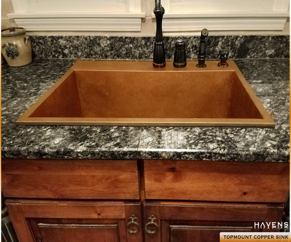 Topmount copper sink with a rear deck for faucets integrated directly into the granite countertops with no modification at all.