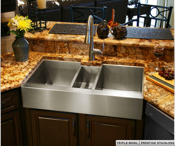 Triple bowl stainless steel farmhouse sink with 3 bowls and a large wash basin on either side. Custom stainless steel farm sink.