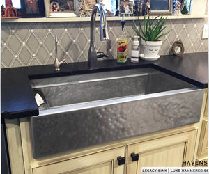 Matte hammered stainless steel farmhouse sink with a rustic appearance. Culinary workstation style sink with a built in ledge for accessories.