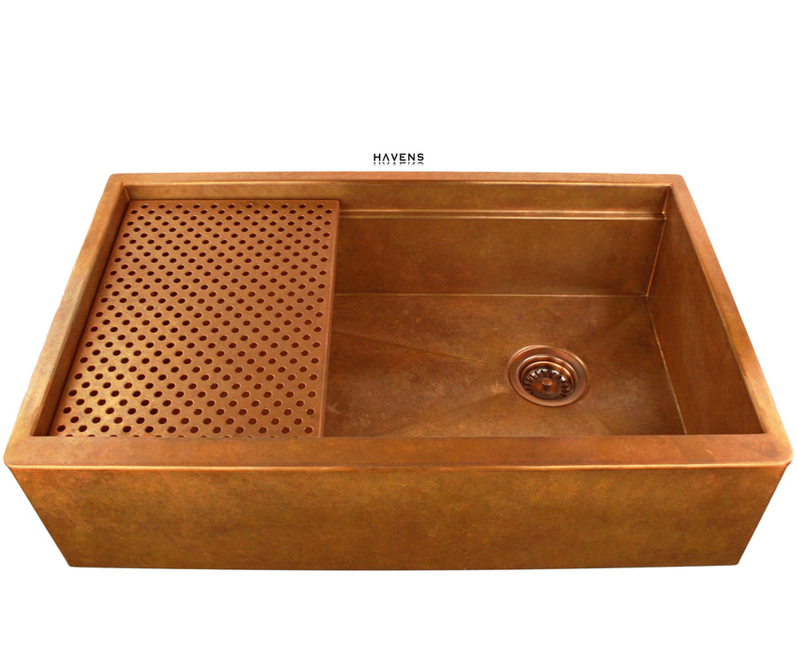 Copper farmhouse workstation sink with a built in ledge and 14 gauge smooth copper finish. Oil rubbed bronze faucet with a farm style sink.