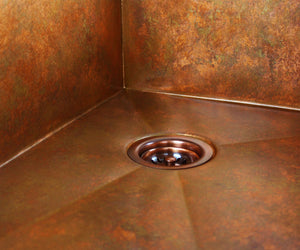 Undermount copper kitchen sink with a disposal drain.