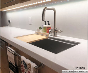 Legacy undermount sink with bamboo cutting board and ledge for advanced sink accessories.