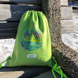 Limegreen Hodag backpack with colored in artwork on a park bench