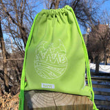 Lime green drawstring backpack featuring white line artwork of sky, trees, water and a Meshipeshu hiding in the waves with a white fabric tab underneath with the word Happy. The bag is sitting on a post in a park.