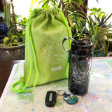 Lime green back pack, grey water bottle and colorful keychain sitting on a map.