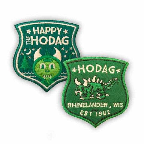 Forest green patch set embroidered with lime green, Kelly green and eggshell white. One patch depicts happy the Hodag smiling with trees, water, stars and the moon behind him and the text at the top reads happy the Hodag and the other patch features a traditional hodag with the text Hodag, Rhinelander, WIS set 1882