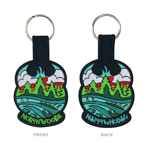 black keychains with colorful embroidery of sky, trees, water and a Meshipeshu hiding in the waves. Front has text Northwoods, back has text Happy the Hodag