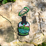 black keychains with colorful embroidery of sky, trees, water and a Meshipeshu hiding in the waves. Front has text Northwoods, back has text Happy the Hodag. Shown sitting on a rock with a green carabiner.