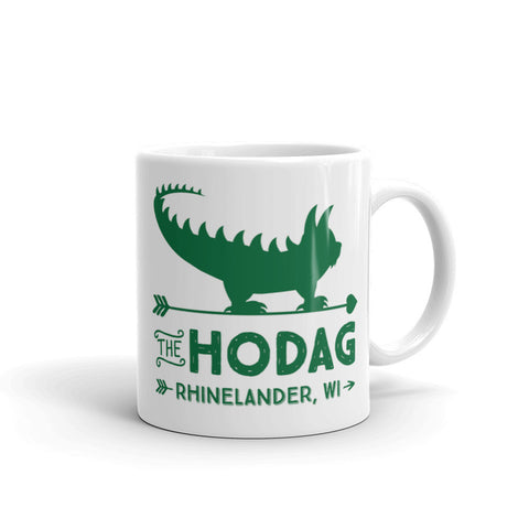 White porcelain coffee mug with green artwork featuring a vintage Hodag standing on an arrow and text that reads 'the Hodag, Rhinelander, wi'