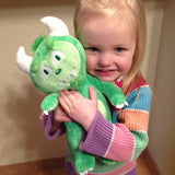 A little girl hugging a Happy the Hodag Plush Toy