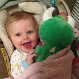 A baby playing with a Happy the Hodag Plush Toy
