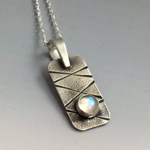 close-up view of one small silver pendant with bezel set moonstone