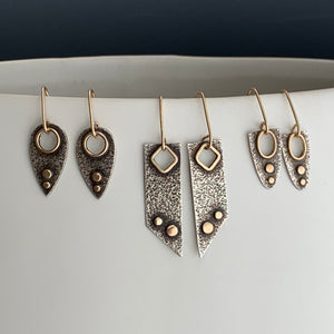 three pairs of modern love style earrings displayed in a row