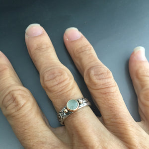 aquamarine ring on silver band with gold setting shown on hand