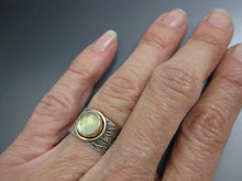 view on hand of sterling and gold ring with prehnite pale green stone