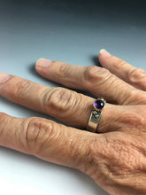 silver and gold and amethyst statement ring shown on hand