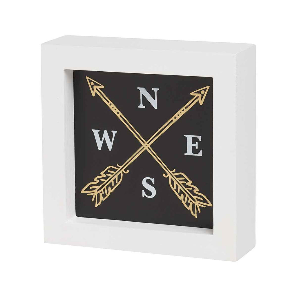 compass with gold arrows on box sign