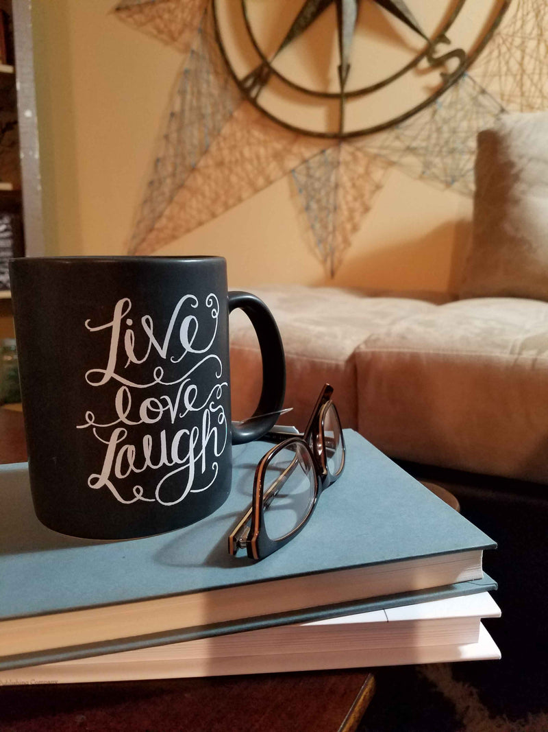 live love laugh black coffee mug with white lettering on coffee table