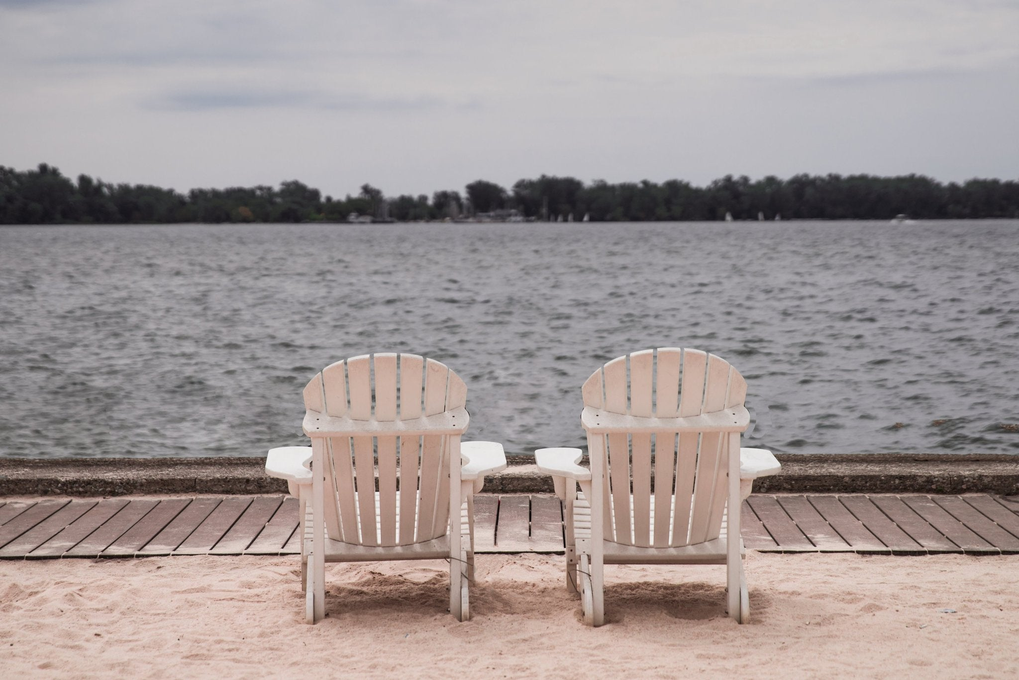 two wood slatted beach chairs in facing water