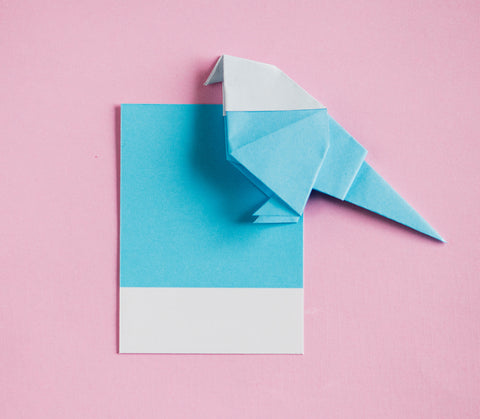turquoise, white, and pink paper origami bird