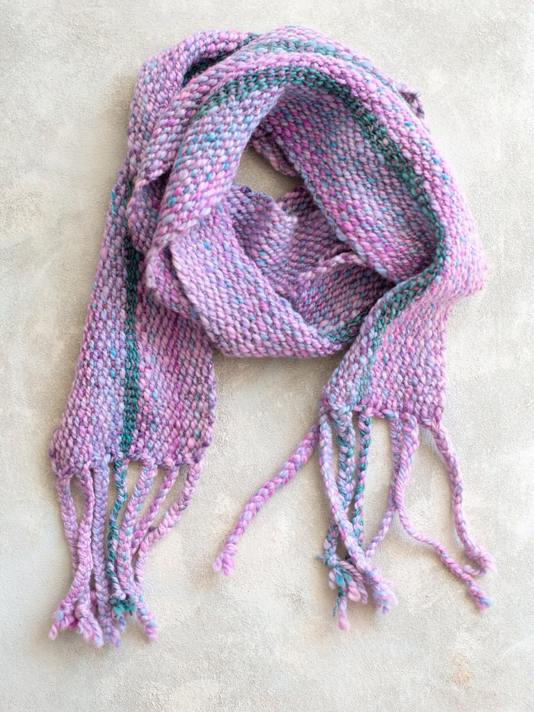 A scarf made from purple and pink yarn with a contrasting stripe of blue and gray yarn running vertically through the weave
