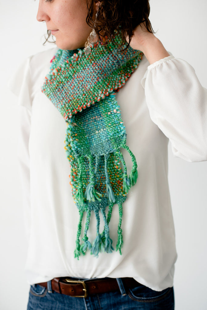 Hand woven scarf made from green and blue yarns with orange, pink, and yellow accents