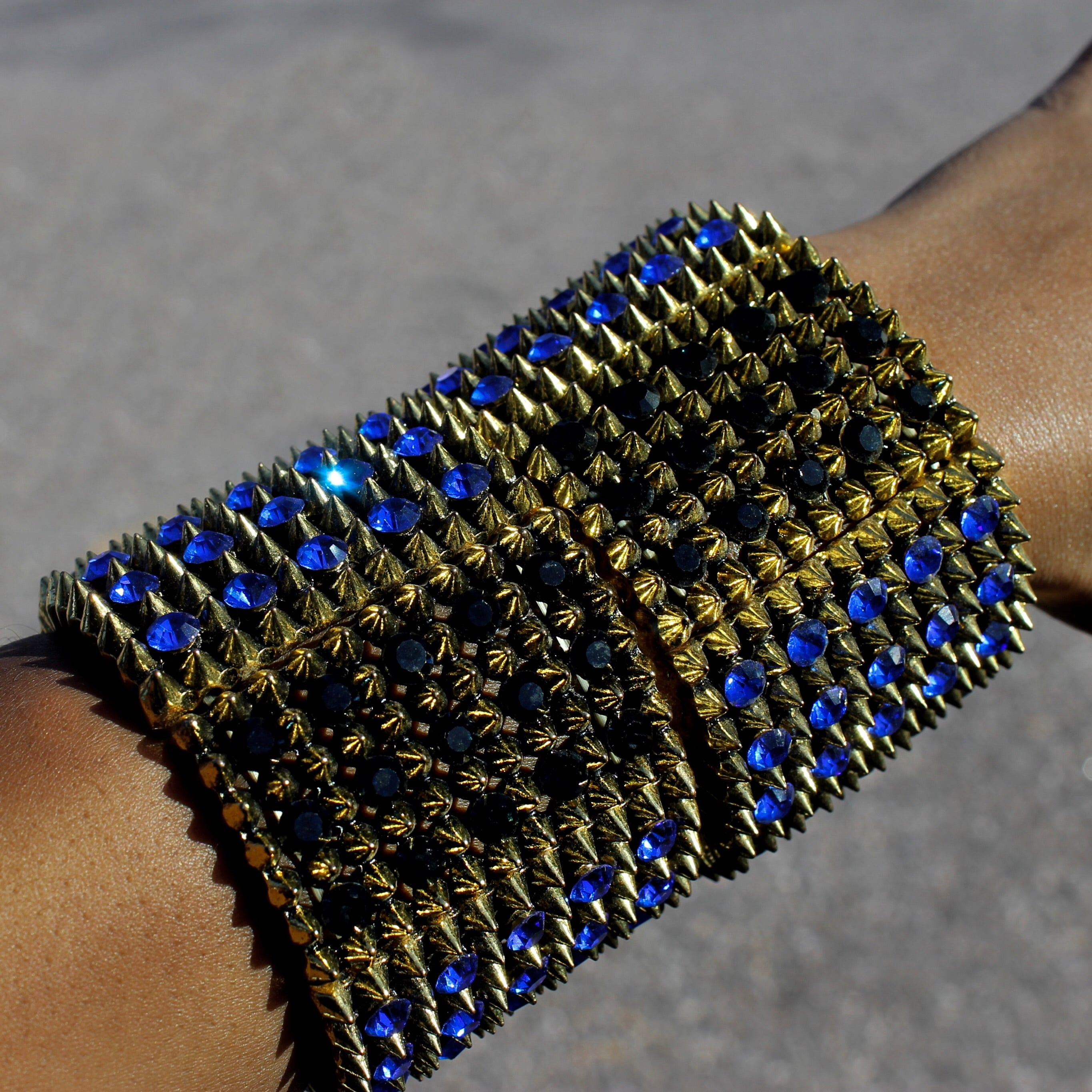 A High Polished Gold Expandable Bracelet featuring Blue and Black Stone Design.