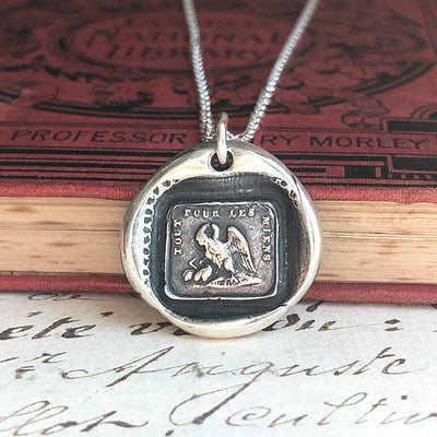 A Mother's Love Wax Seal Necklace on a stack of antique books.