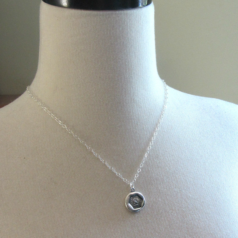 Our new mommy wax seal necklace around a mannequin.